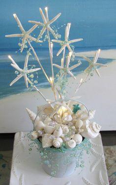 Centro de mesa con caracolas y estrellas de mar. Para una boda cerca del mar o con esta temática. Tonos blancos y azules