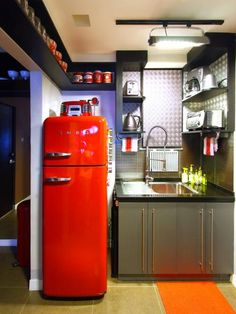 A red refrigerator and vintage canisters pop against this retro kitchen's otherwise monochromatic color scheme. Black wood shelving lines the space and the stainless steel sink, while metal geometric wall panels serve as a backsplash.