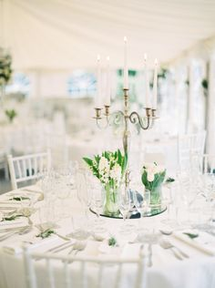 elegant tented wedding reception in all white   white chiavari chairs, white table cloths and napkins   trio of white floral centrepieces on top of round mirros and silver candelabras   A Springtime French Chateau Wedding
