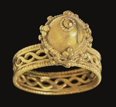 A BYZANTINE GOLD FINGER RING   CIRCA 7TH CENTURY A.D.   The openwork hoop composed of a guilloche of plain wire framed by plain and beaded wire, the high bezel a series of drop-shaped petals of beaded wire supporting a guilloche of plain wire with granules dispersed throughout, capped with a sheet hemisphere fringed with beaded wire and granulated triangles, a central granule at the peak with a beaded wire fringe