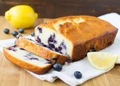 A landscape photo of Blueberry Lemon Yogurt Cake. There are two slices cut from the load, and the cake is ona linen napkin. It is set on a medium brown wood countertop. There is a lemon in the background and 6 blueberries.