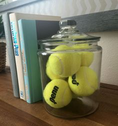 These tennis balls in a glass container are a great way to decorate a sports theme bedroom, and also make for a great book stopper. #Tennis #Decor Home decor at The Trails at Pine Ave, San Bernardino.