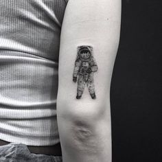 Single needle astronaut tattoo on the back of the right arm.
