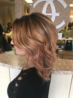 Hand painted rose gold golden copper blonde balayage highlights on dark brown root lived in rooted hair curls waves medium length hair