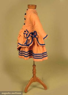 """Child's bustle dress, c1869; Two-piece apricot wool twill, long fitted polonaise bodice with elaborate bows and ties at sides edged in bright blue wool, skirt with three blue bands near hem, knife pleated, both lined in cotton, Ch 24"""", W 22"""", Skirt L 13.5"""""""
