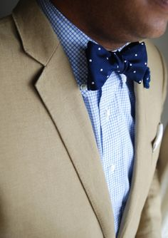 Tan jacket, light blue plaid shirt, navy bow tie