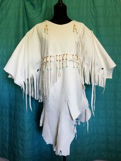 This beautiful white buckskin long shirt or tunic is hand-crafted and can be worn everyday or for Pow Wow Regalia, Rendezvous, Western wear and other occasions. Made of beautiful, elk hide, it is a heavy weight garment. It has an over-the-head fit and fringe on the sleeves and across the front.  SIZING: Mens Small to Medium and Womens Small to Large. This white elk hide tunic measures 20 across from side seam to side seam of shirt measured at the bottom of the arm hole, which totals 40…