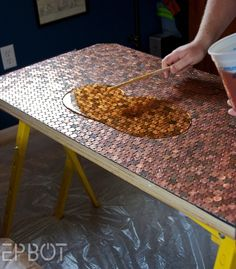 DIY penny table... amazing. Recycling old coins at its best! Table underneath window.