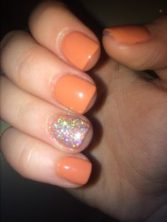 Orange nails with multicolored glitter on ring finger