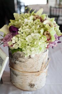 white hydrangeas, purple roses, green orchids all in a bark covered vase. so great.