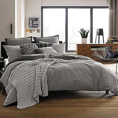 Kenneth Cole Reaction Home Oxford Comforter in Grey Stripe and pillows with pops of purple, teal or navy.