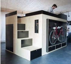 Een mooie tiny house oplossing midden in deze woning van Nils Holger Moormann waar slapen koken wonen en berging in 1 meubel van multi- & betonplex worden geïncorporeerd.