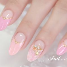 Pink almond shaped nails with gold accents