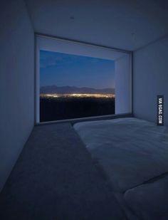 Quarto de apartamento, com cama na altura de piso forrado e parede de vidro para fora do prédio.
