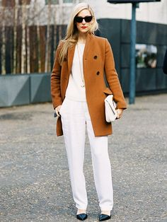 Joanna Hillman wears a rich camel coat over a cream sweater, wide-leg pants and her signature red lip