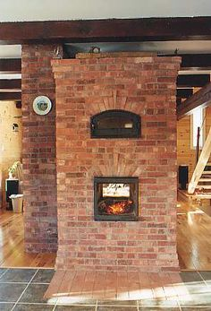 Finnish style contraflow masonry heater with see through fire box (ie. the masonry heater has an opening and door on both front and rear faces). The secondary combustion chamber bake oven opens into the kitchen. Recycled brick from Montreal c.