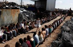 A model presents a creation from the Cavalera Summer 2012/2013 collection in a junkyard during Sao Paulo Fashion Week