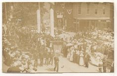Citizens Fire Company marching in the 1907 Mechanicsburg Centennial celebration parade. Franklin Hall is in the back and a stand selling ruby glass souvenirs can be seen at the lower right.