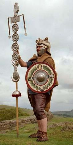 A first century signifer. His armour and helmet are covered in a wolf skin and he also carries a small circular shield.  The signifer takes his name from the type of standard he carries, the signum. The signum was used as the standard for each maniple in the legion (a maniple consisted of two centuries).