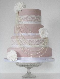 This four tier vintage style wedding cake has been covered in a coloured icing to compliment the lace and satin ribbon around each of the tiers. The pearl beaded necklace is draped down the front of the cake and secured with delicate sugar flowers.