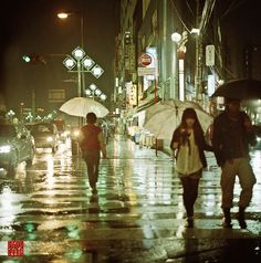 City life in the rain, people with umbrellas walking down the streets