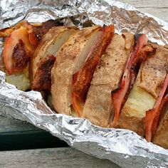 Doing this (or a close fascimilie of this:Potato Boat with Ham, Cheese & Bacon | 27 Delicious Recipes To Try On Your Next Camping Trip