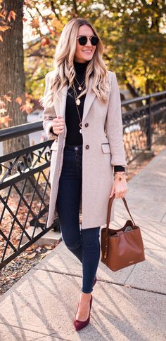 #fall #outfits woman's brown notch-lapel coat, brown leather handbag, black sunglasses, blue skinny jeans, black turtleneck shirt and pair of red bow accent flat shoes