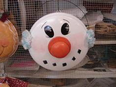Snowman with earmuffs on recycled pot lid