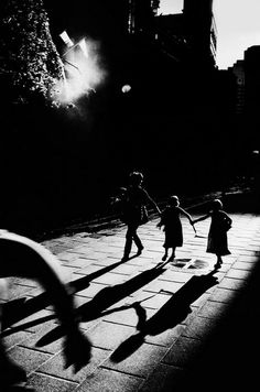 A mother and her twin daughters hold hands while walking up the deserted business district of martin place on a Sunday in Sydney, Australia, 1998. Photo by Trent Parke.