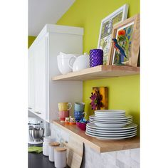 Floating shelves offer clean lines and open storage in a kitchen. A bright wall color is enhanced by natural stone subway tiles.