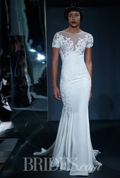 Brides.com: Mark Zunino for Kleinfeld - 2014. Style 80, short sleeved sheath wedding dress of floral lace applique on illusion with silk crepe skirt, Mark Zunino for Kleinfeld