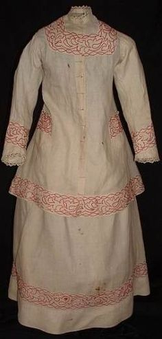 Girl's linen summer outfit with red wool soutache trim, c. 1875. The outfit consists of a skirt and a long paletot-type jacket which has ties on the inside to adjust the back gathers for the size of the bustle.