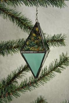 Stained Glass Diamond Ornament or Sun Catcher using green mirror and a green/copper/gold reflective glass called Van Gogh.  Ornaments made with reflective glass are particularly beautiful as sun catchers or decorations. This diamond measures 2 wide x 3 deep x 5 high. It is finished in a black patina and is waxed and polished.  All ornaments come with a decorative hanger and gift bag.  This diamond shape is also called an Octahedron.  The Octahedron represents the element of Air and...
