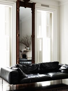 black leather sofa, white walls, full length mirror