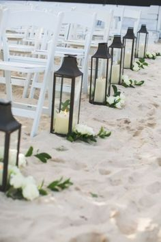 Lanterns and flowers line the beach aisle
