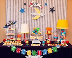 Goodnight Moon Dessert Table: For this colorful dessert table, a striped backdrop — an inexpensive shower curtain from Target — and a navy-blue linen worked well with the Goodnight Moon theme and made the bright table details and desserts really pop. A cow jumping over the moon was hung with fishing wire for a whimsical touch hanging above the table — another inexpensive and fabulous touch, since the art file was downloaded and printed at home. Source: Hostess with the Mostess