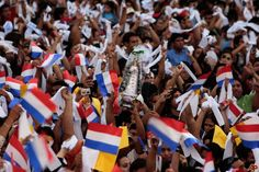 people of Paraguay parade with their flag in the air.
