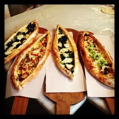 "Pide | Often called ""Turkish Pizza,"" Pide is a boat-shaped flatbread served with a variety of toppings, often minced meat or spinach and cheese."