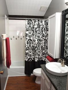 Gray Modernity  For less than $500, RMS user smwagne turned a drab 1970s bathroom into a modern space. White cabinetry and tile tub surround add lightness to the deep gray walls and black-and-white shower curtain. Deep red towels add a splash of color and chic style.