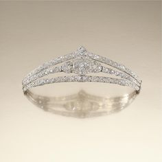 DIAMOND DIADEM TIARA, CIRCA 1919 Designed as a diadem composed of a series of graduated chevron panels, centring on an oval plaque  set between arched shoulders, embellished throughout with circular-cut and cushion-shaped diamonds, inner circumference approximately 210mm, signed Paris, Londres and numbered, later fitted case by Antrobus 6-8 Old Bond Street, London, W1. 42,000 GBP