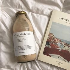 a photo of a bottle of coffee and a book against a bedspread