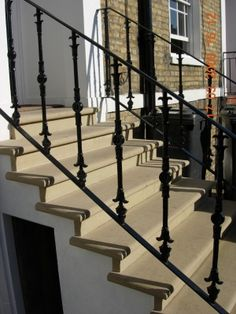 Bull-nosed sawn Yorkstone steps with architectural ironwork handrails installed by English City Stone.