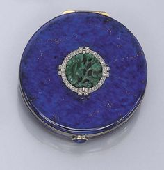 AN ART DECO ENAMEL, JADEITE AND DIAMOND COMPACT   The circular blue mottled enamel, imitating lapis lazuli, case set with a central carved floral motif jadeite in a rose-cut diamond surround to the enamel push-piece opening to reveal a fitted mirror, circa 1925, 5.2 cm. diameter, with French assay mark