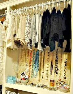 A personal jewelry boutique inside a closet: Bracelets in stylish bowls, watches on a tray and necklaces beautiufully hung.