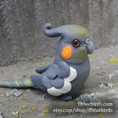 Show some cockatiel love with a cute miniature figurine. She is handmade from polymer clay, with two drops of resin to accent her eyes. Her orange cheeks are styled in a playful spiral, and a touch of
