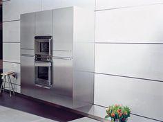kuchnia wisząca B3 81 stalowa zabudowa wysoka z piekarnikami i chłodziarką wisząca przy białych panelach szklanych