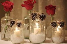 frascos de vidrio con velas y piñas de pino