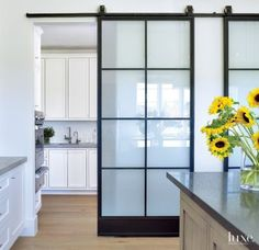 Sliding iron doors provide separation in a Houston residence's #kitchen. | See MORE at www.luxesource.com