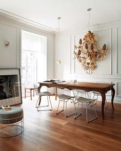 Beautiful juxtaposition of wire Bertoia chairs with a French farmhouse dining table, and a statement sculptural piece on the paneled walls.