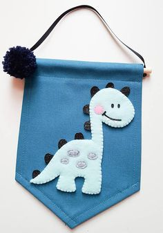 This is a lovely mini wall banner which would look super cool in your childs nursery or playroom ♥ This banner is made from white heavy canvas material which has been machine stitched for stability on all sides. The dinosaur is hand cut from non shedding glitter fabric, felt and